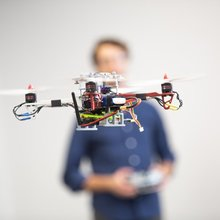 Drone with guy and controller in background